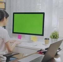 ویدیو فوتیج زنی که با صفحه سبز مانیتور کار میکند